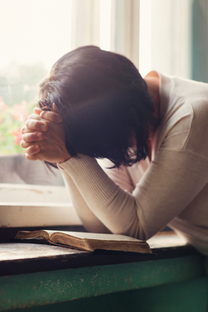 personas orando: Mujer irreconocible leyendo la Biblia y orando