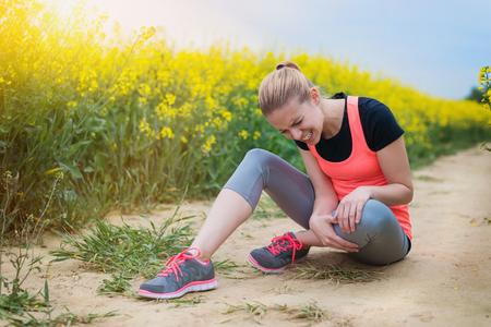 Молодая женщина, имеющие травмы на ее бежать снаружи в поле весной канолы Фото со стока