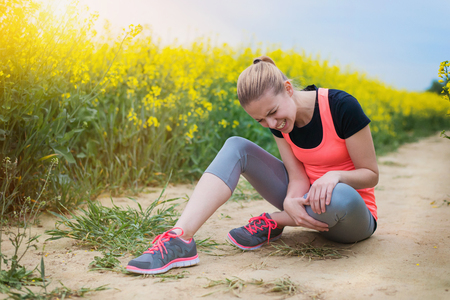 mujer joven que tiene una lesión en su corral al aire libre en el campo de colza de primavera