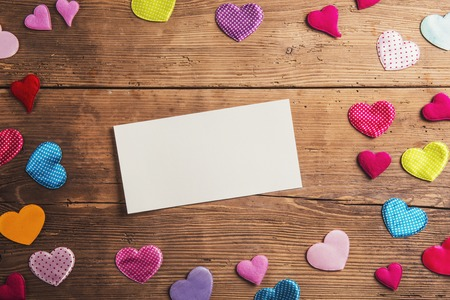 Empty paper sheet and colorful fabric hearts. Studio shot on wooden background. Imagens