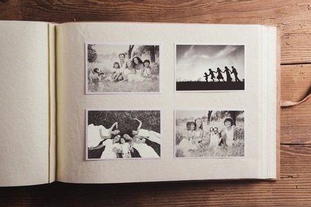 albums: Photo album with black and white family pictures. Studio shot on wooden background. Stock Photo
