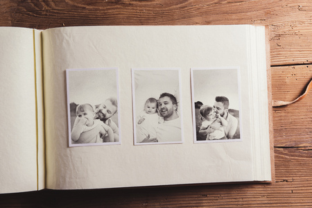 photo pictures: Photo album with black and white family pictures. Studio shot on wooden background. Stock Photo