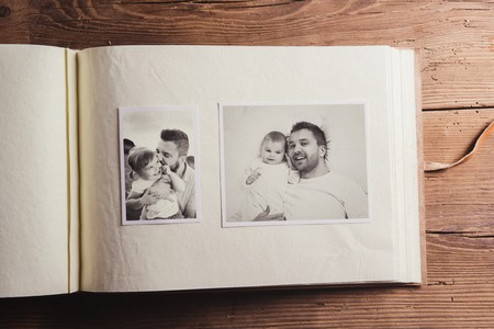 black and white image: Photo album with black and white family pictures. Studio shot on wooden background. Stock Photo