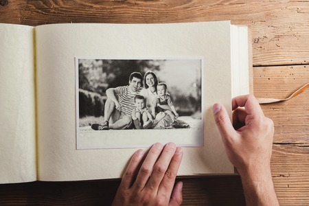Photo album with black and white family pictures. Studio shot on wooden background. 免版税图像