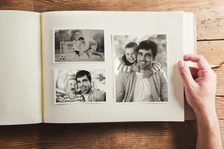 Photo album with black and white family pictures. Studio shot on wooden background. Foto de archivo