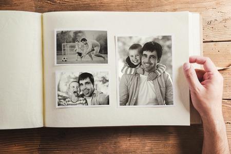 Fotoalbum met zwart-wit familiefoto's. Studio opname op houten achtergrond.