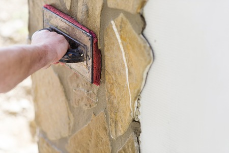 stone work: Mason putting decorative natural stones on a wall