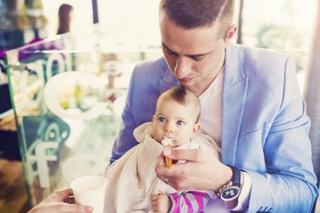 Mooie jonge gezin plezier in cafe