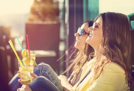 Schöne junge Frauen mit Getränken Spaß