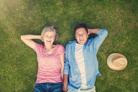 happy seniors: Beautiful senior woman and man lying on the gras Stock Photo