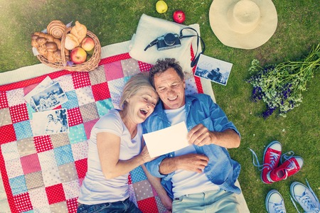 picnic blanket: Beautiful senior woman and man lying on a colorful blanket Stock Photo