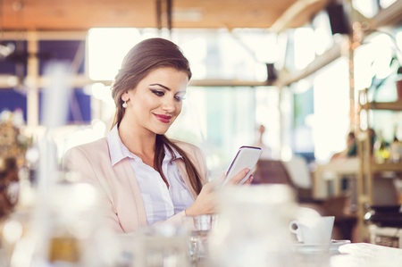 brunette woman: Beautiful young businesswoman with smart phone in cafe