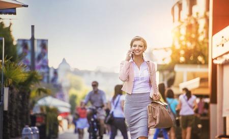 Aantrekkelijke jonge vrouw met slimme telefoon lopen in de stad