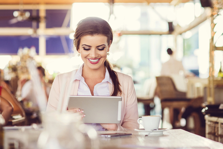 Beautiful young businesswoman with tablet in cafe
