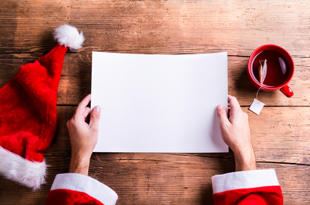 wish  list: Santa Claus holding an empty wish list in his hands Stock Photo