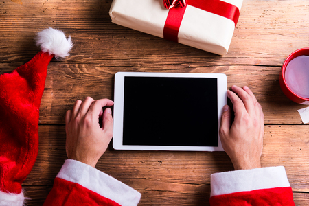 wishlist: Santa Claus holding tablet in his hands