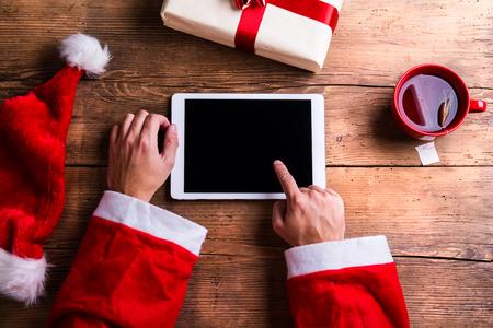 Le Père Noël tenant dans ses mains la tablette Banque d'images