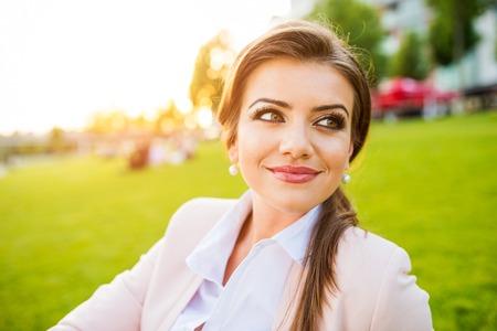 pelo largo: Hermosa mujer de negocios joven sentado en un parque Foto de archivo
