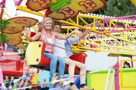 theme parks: Senior couple having fun in amusement park