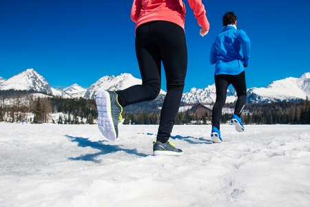jogging in nature: Young couple jogging outside in sunny winter mountains