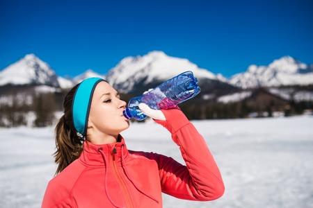 tomando agua: Mujer joven que activa al aire libre en las montañas soleados de invierno