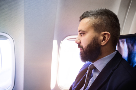 busy beard: Young handsome businessman sitting inside an airplane Stock Photo