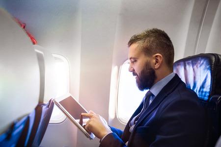 EMPRESARIO: Apuesto hombre de negocios joven con la tablilla que se sienta dentro de un avión Foto de archivo