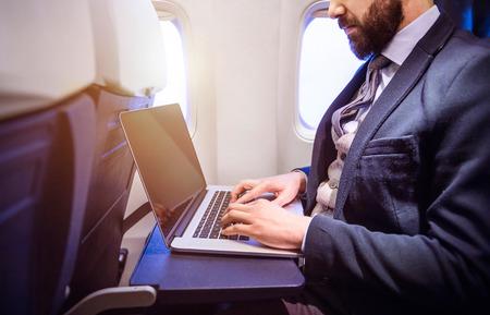 飛行機の中に座ってノートを認識できない青年実業家