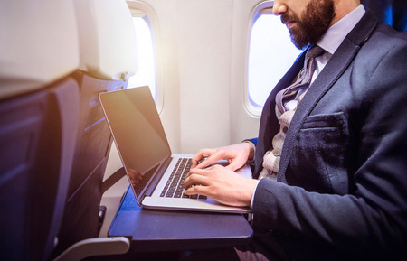 Unrecognizable young businessman with notebook sitting inside an airplane Stockfoto