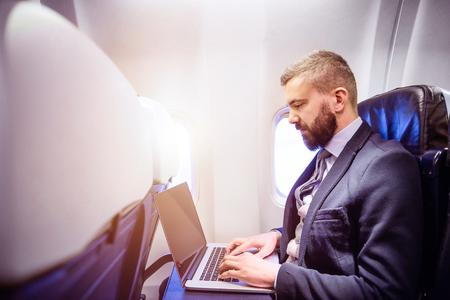 Apuesto hombre de negocios joven con el cuaderno que se sienta dentro de un avión