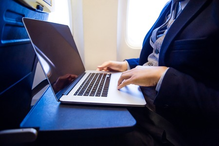 aircraft: Unrecognizable young businessman with notebook sitting inside an airplane Stock Photo