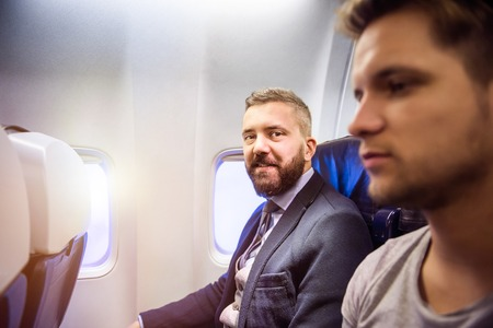 corporate airplane: Two young handsome men sitting inside an airplane Stock Photo
