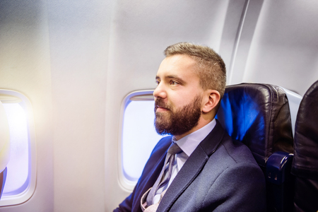beard man: Young handsome businessman sitting inside an airplane Stock Photo