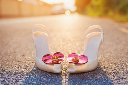 Bridal shoes and wedding rings laid on the ground