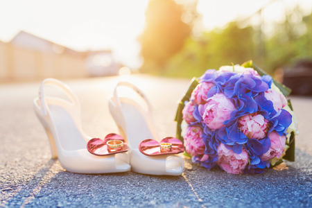 wedding rings: Wedding bouquet and shoes with rings laid on the ground