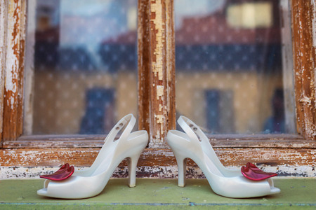 old windows: Bridal shoes with red hearts laid on window parapet