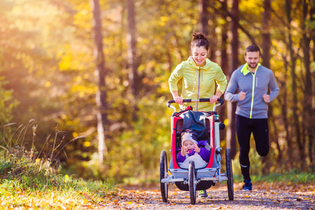 family exercise: Beautiful young family running outside in autumn nature Stock Photo