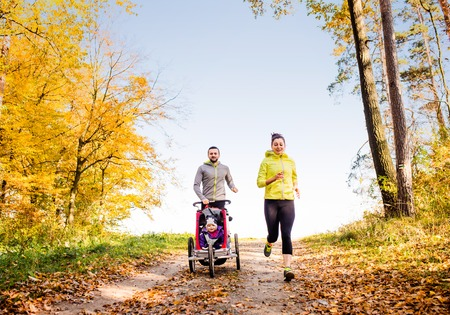 smiling man: Beautiful young family running outside in autumn nature Stock Photo