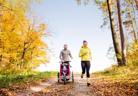 Bella giovane famiglia esecuzione all'esterno in autunno la natura