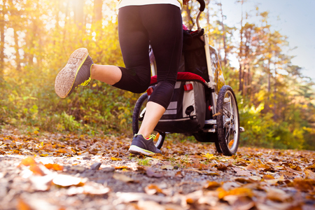 sports training: Unrecognizable young mother with her daughter running outside in autumn nature