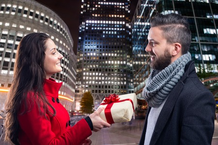men and women: Young beautiful couple buying gifts in the city