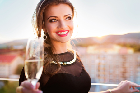 black belt: Attractive young woman with a drink on a terrace of a bar Stock Photo