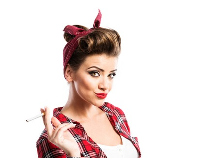 sexy girl smoking: Beautiful young woman with pin-up make-up and hairstyle holding a cigarette. Studio shot on white background