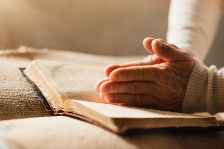 manos: Mujer irreconocible que sostiene una biblia en sus manos y la oración Foto de archivo