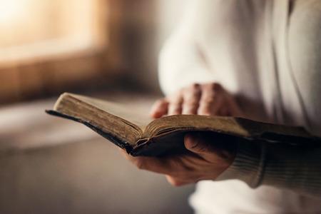 biblia: Mujer irreconocible que sostiene una biblia en sus manos y la oración Foto de archivo