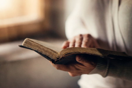 Mulher Unrecognizable que prende uma Bíblia em suas mãos e orando Banco de Imagens
