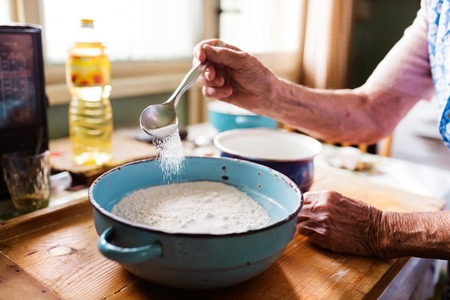 Senior woman baking pies in her home kitchen. Measuring ingredients. Stok Fotoğraf - 49172111