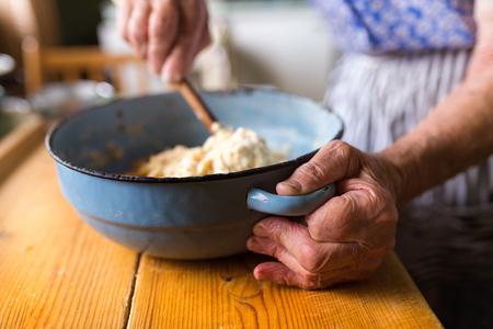 damas antiguas: Empanadas hornada de la mujer de alto nivel en su cocina en casa. Mezcla de ingredientes. Foto de archivo