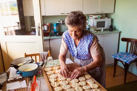 cocina vieja: Empanadas hornada de la mujer de alto nivel en su cocina en casa. Cortar círculos de masa cruda.