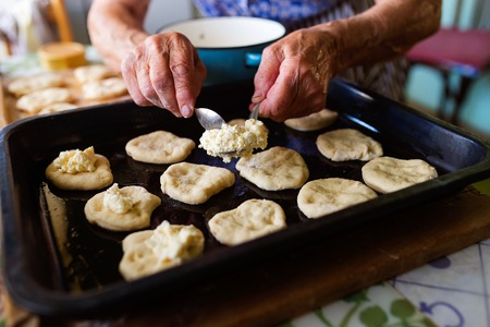 cookie sheet: Senior woman baking pies in her home kitchen.  Filling the buns with cottage cheese.